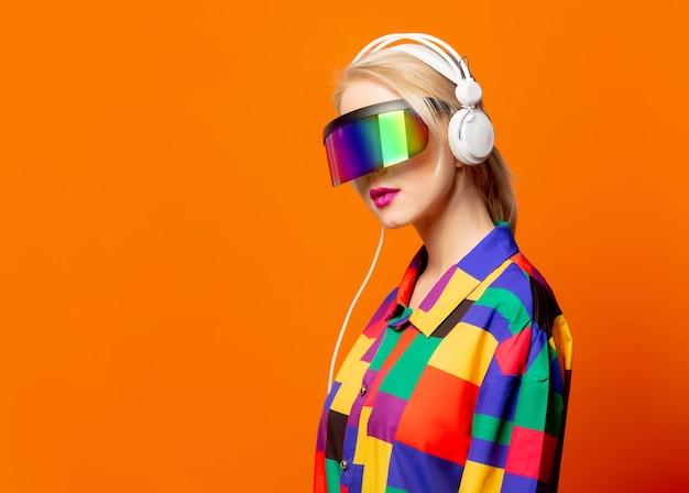 Style blonde dans des vêtements des années 90 avec des lunettes et des écouteurs vr sur orange