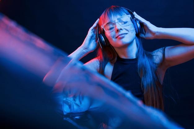 Style cyberpunk. studio tourné en studio sombre avec néon. portrait de jeune fille