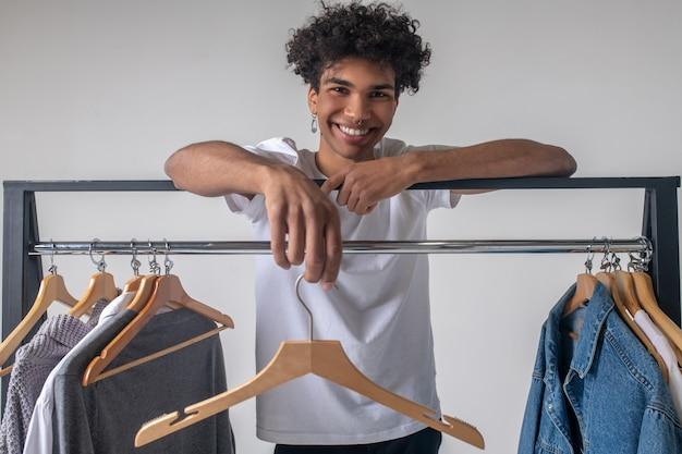 Style décontracté. . jeune homme afro-américain près de cintres avec des vêtements souriant