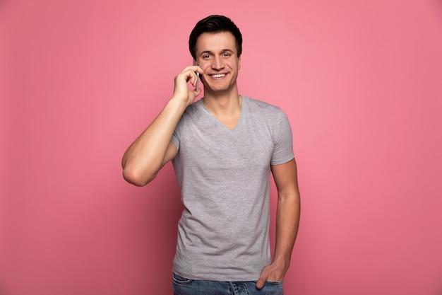 Style décontracté. séduisante jeune homme regarde la caméra avec un grand sourire, tout en parlant au téléphone et en tenant sa main gauche dans une poche.