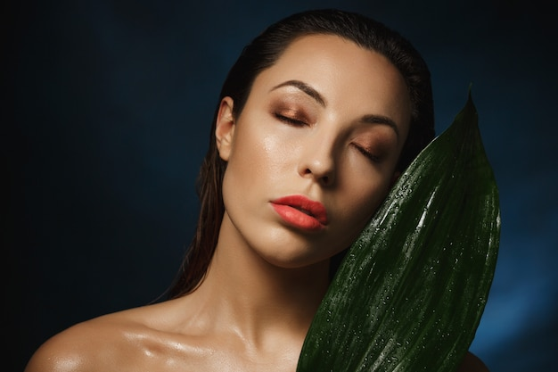 Style exotique. photographie de mode. femme nue, penchant, à, plante verte.