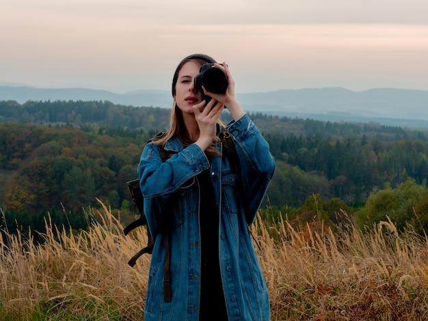 Style femme avec appareil photo et sac à dos à la campagne avec les montagnes
