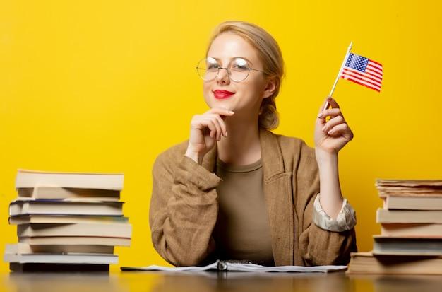 Style femme blonde assise à table avec des livres autour et détient le drapeau américain sur jaune