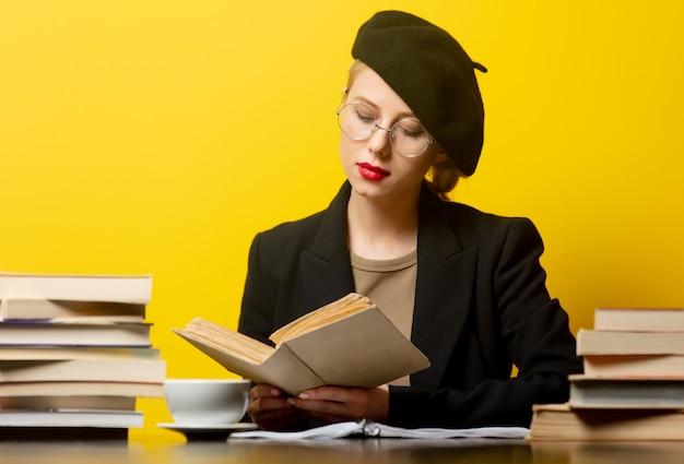 Style femme blonde en béret assis à table avec des livres autour sur jaune