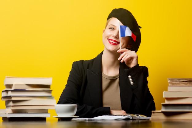 Style femme blonde en béret avec drapeau français et livres autour sur jaune