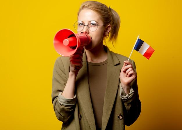 Style femme blonde en veste avec drapeau français et mégaphone sur jaune