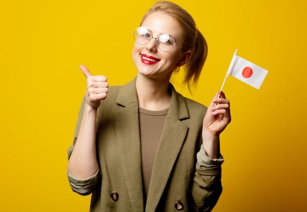 Style femme blonde en veste avec drapeau japonais sur jaune
