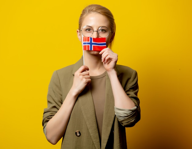 Style femme blonde en veste avec drapeau norvégien sur jaune