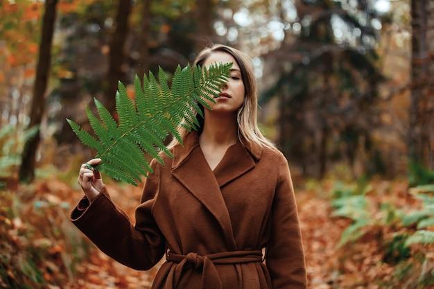 Style femme avec branche de fougère dans une forêt d'automne