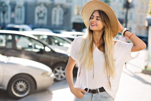 Style femme heureuse, amusez-vous dans la rue. heureuse jeune femme regarde de côté et tient son chapeau.
