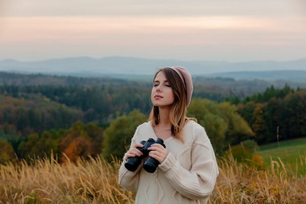 Style femme avec des jumelles à la campagne avec les montagnes
