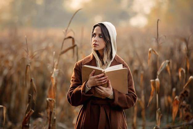 Style femme avec livre sur un champ de maïs en automne
