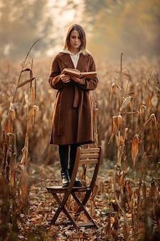 Style femme avec livre rester sur une chaise sur un champ de maïs en automne
