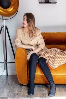 Style femme avec maquillage assis dans le canapé