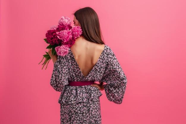 Style de femme en robe avec des fleurs sur fond rose