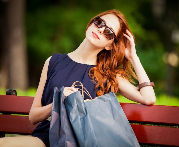 Style femme rousse assise sur le banc avec des sacs