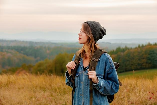 Style femme en veste en jean et chapeau avec sac à dos dans la campagne avec les montagnes