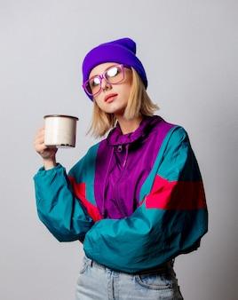 Style femme en vêtements punk des années 90 avec une tasse de café