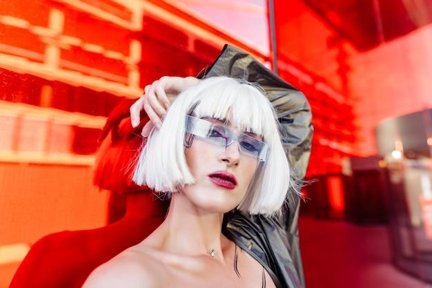 Style futuriste. femme à lunettes et près d'un bâtiment futuriste rouge.