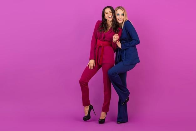 Style haute couture deux femmes attrayantes souriantes sur un mur violet dans des costumes de soirée colorés et élégants de couleur violet et bleu, amis s'amusant ensemble, tendance de la mode