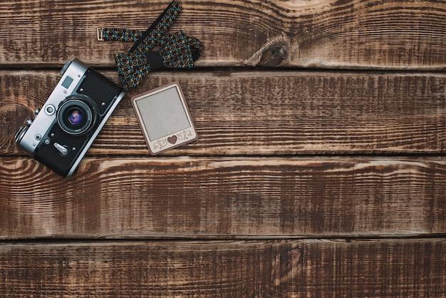 Style hipster. appareil photo rétro et noeud papillon sur une table en bois. vue de dessus