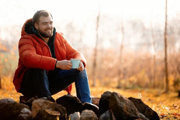 Style homme en doudoune avec une tasse de café assis près d'un feu de joie