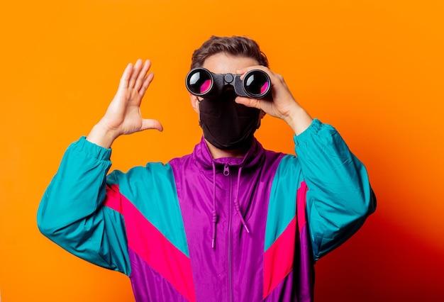 Style homme en masque facial et survêtement des années 80 avec jumelles