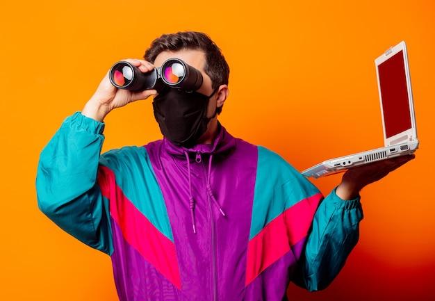 Style homme en masque facial et survêtement des années 80 avec ordinateur portable et jumelles