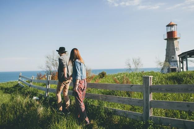 Style indie jeune couple hipster amoureux marchant dans la campagne