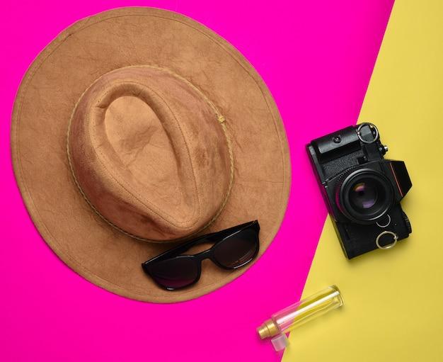 Style de mode créatif plat avec appareil photo, lunettes de soleil, bouteille de parfum et chapeau de feutre sur fond de couleur pastel, wanderlust.