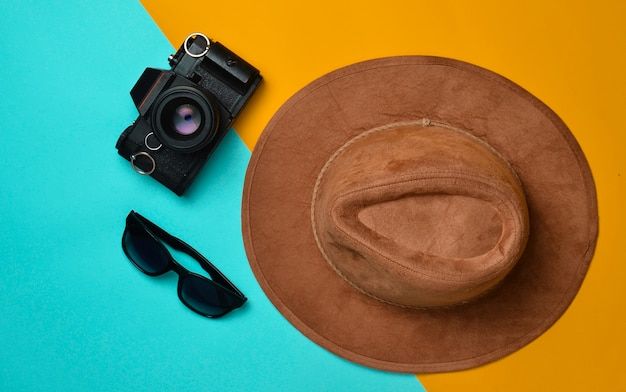 Style de mode créatif plat avec appareil photo, lunettes de soleil et chapeau en feutre sur couleur pastel, wanderlust.