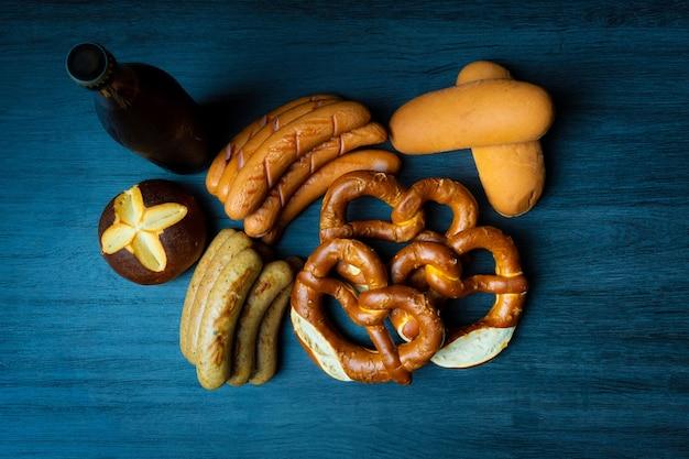 Style de nourriture sombre saucisses oktoberfest bretzels pain et bière sur table en bois