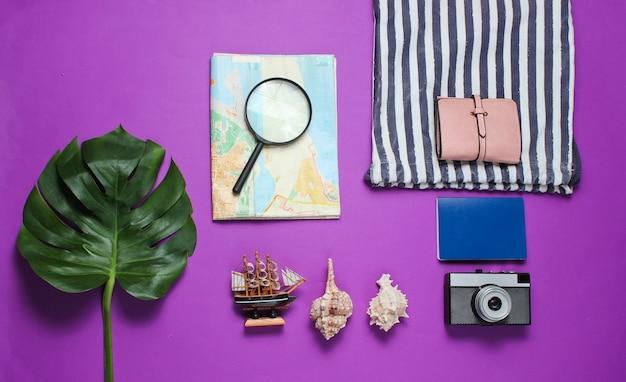 Style plat laïque de voyage encore minimaliste. accessoires de voyageur touristique sur fond violet avec feuille de monstera tropical.