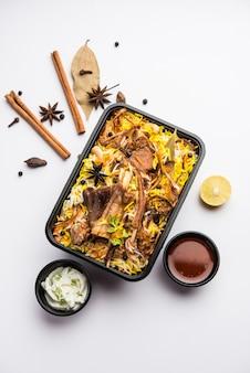 Style de restaurant gosht ou mutton biryani ou pulao emballé pour la livraison à domicile dans une boîte ou un conteneur en plastique avec raita et salan