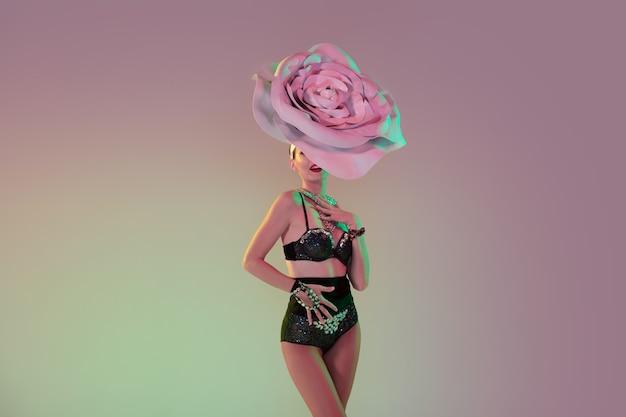 Style rétro. jeune danseuse avec d'énormes chapeaux floraux en néon sur mur dégradé. modèle gracieux, femme dansant, posant. concept de carnaval, beauté, mouvement, floraison, mode printanière.