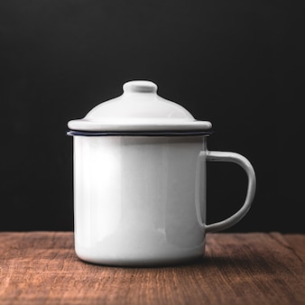 Style de tasse vintage sur fond en bois. tasse à thé rétro en étain.