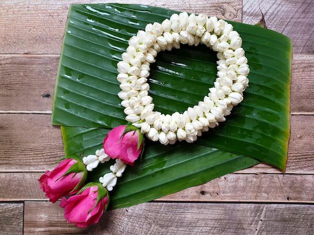 Style thaïlandais de guirlande de jasmin sur feuilles de bananier et fond en bois