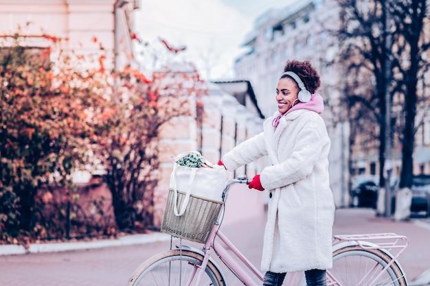 Style urbain. femme joyeuse gardant le sourire sur son visage tout en écoutant de la musique dans des écouteurs