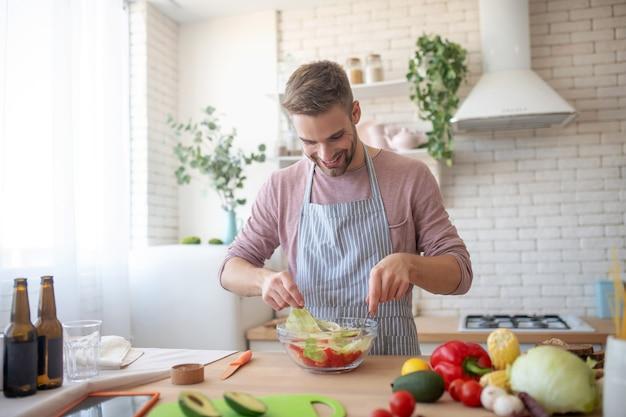 Style végétarien. un homme souriant prépare une délicieuse salade de légumes