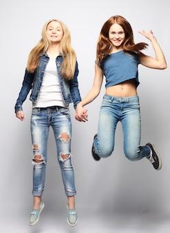 Style de vie et concept de personnes: filles heureuse sautant par-dessus bq blanc