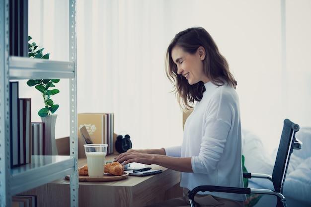 Style de vie femme travaillant en tapant sur un ordinateur portable dans une chambre élégante à la maison