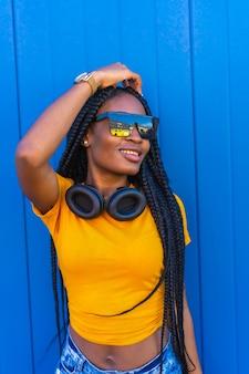 Style de vie, fille noire aux longues tresses, en t-shirt jaune et lunettes de soleil. fille sexy et dj avec un casque souriant