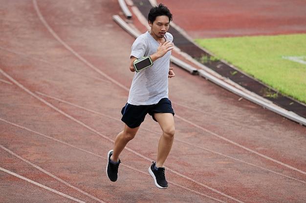 Style de vie de jeune coureur de l'homme asiatique en bonne santé en cours d'exécution sur circuit