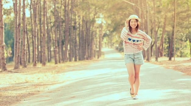 Style vintage jeune jolie fille sur une route de campagne