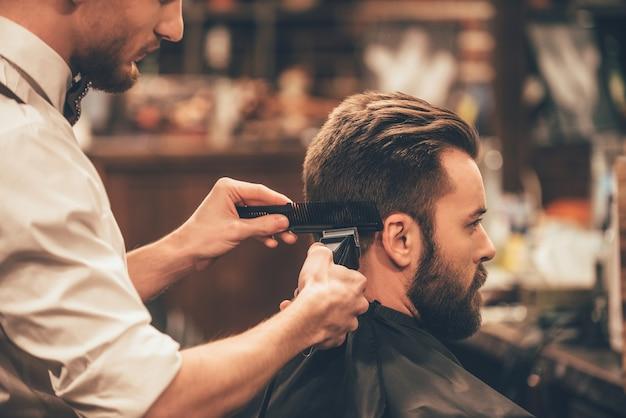 Stylisme professionnel. bouchent la vue latérale du jeune homme barbu se coupe les cheveux