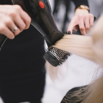 Styliste anonyme séchant les cheveux avec la brosse