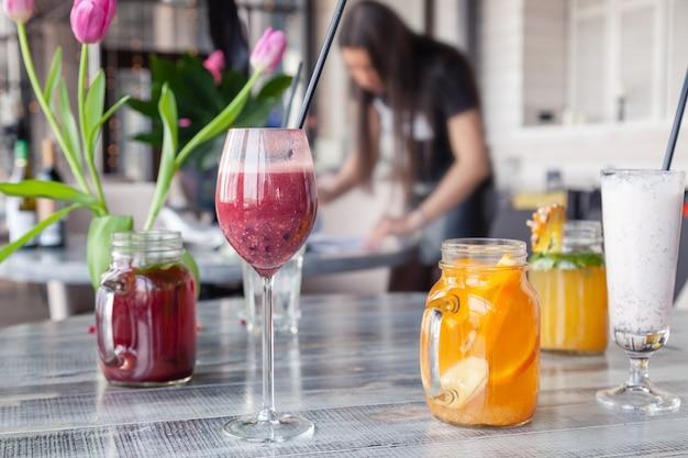 Le styliste culinaire et le photographe décorer, se préparant à tourner divers cocktails, milkshakes, smoothies, vase de tulipes à fleurs sur la table.