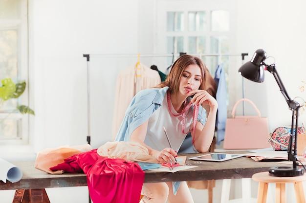 Styliste femme travaillant en studio assis sur le bureau