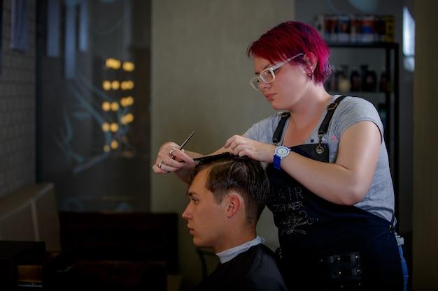 Styliste fille fait une coupe de cheveux à un jeune homme dans un salon de beauté.