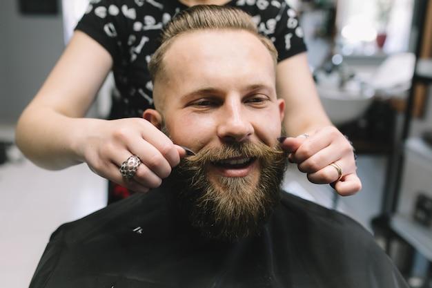 La styliste garde la moustache de l'homme barbu brutal dans le salon de coiffure.